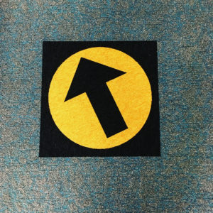 Wayfinding carpet tile replacement with black & yellow arrow